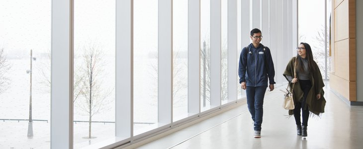 A female and a male student are walking besides each other in the bright corridor of the Waterfront campus and talking to each other while laughing.